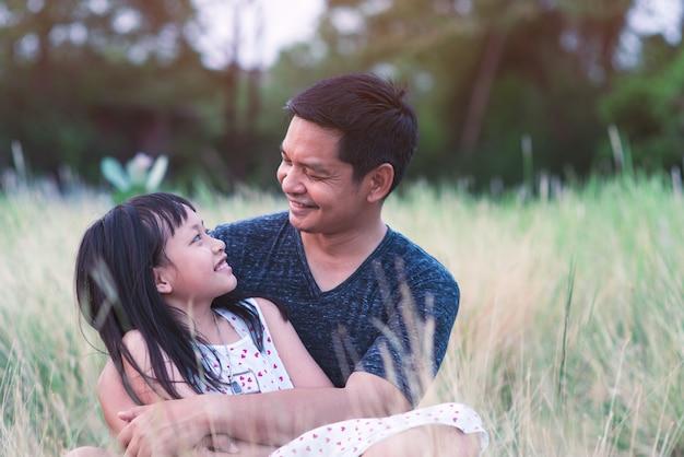 Pai e filha se abraçando na natureza verde com amor