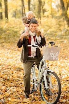 Pai e filha se divertem na mesma bicicleta. sessão de fotos de outono.