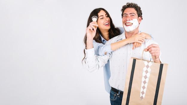 Pai e filha se divertindo com espuma de barbear e presente