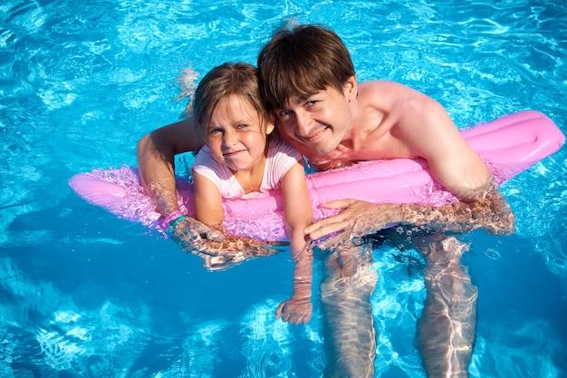 Pai e filha se divertindo na piscina com o inflável rosa