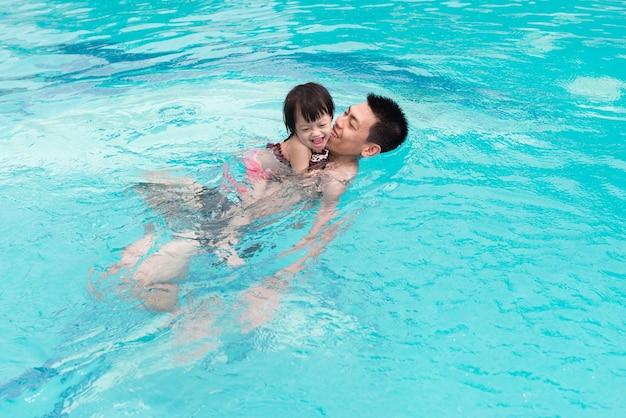 Pai e filha se divertindo na piscina. férias de verão e conceito de férias