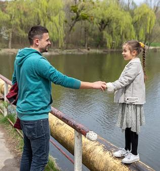 Pai e filha se olham nos olhos e se dão as mãos enquanto caminham pela floresta no início da primavera.