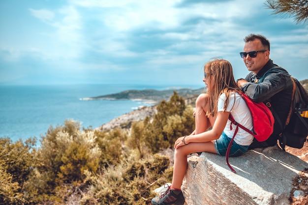 Pai e filha sentada na beira do penhasco à beira-mar