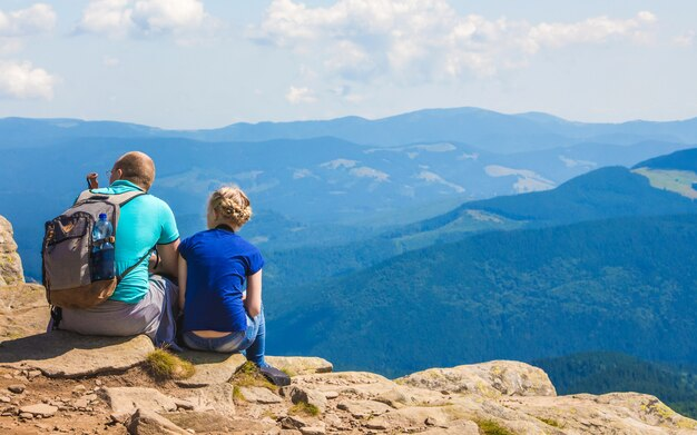 Pai e filha sentado em uma pedra nas montanhas azuis