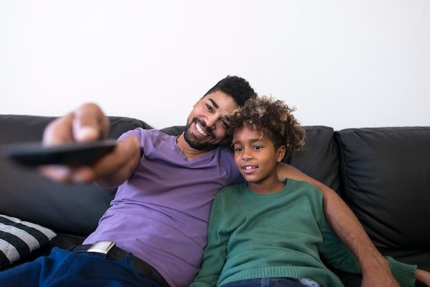 Pai e filha sentados em um sofá confortável assistindo televisão