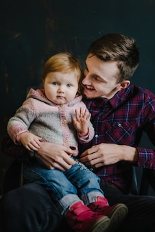 Pai e filha sentados na velha poltrona contra o pano de fundo da parede