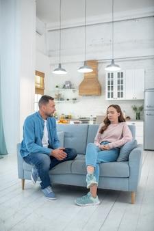 Pai e filha sérios e silenciosos, olhando um para o outro, sentados no sofá.