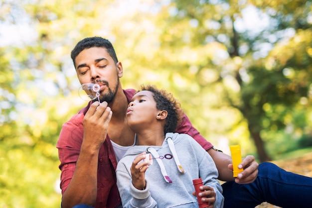 Pai e filha soprando bolhas de sabão se divertindo juntos