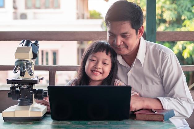 Pai e filha sorrindo e aprendendo em casa com laptop e microscópio