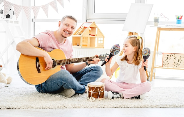 Pai e filha sorrindo e tocando instrumentos musicais na sala das crianças