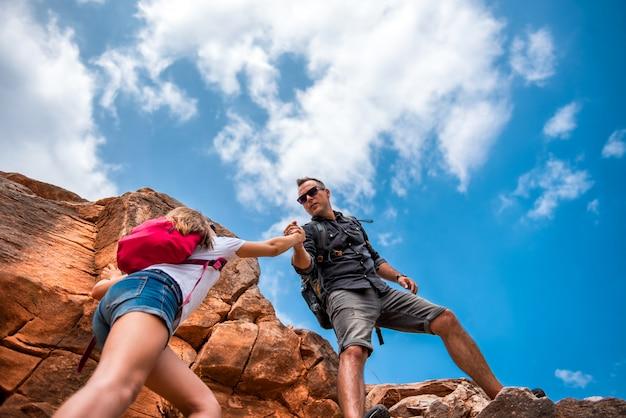 Pai e filha subindo no penhasco