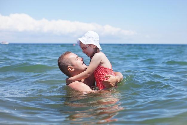Pai e filha tomando banho, família feliz descansando à beira-mar