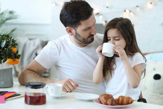 Pai e filha tomando café da manhã na cozinha