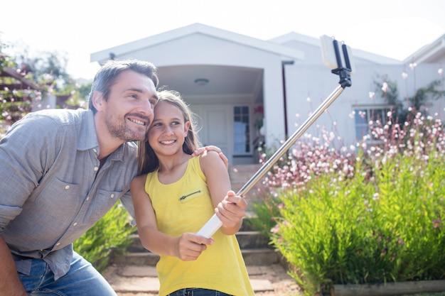 Pai e filha tomando uma selfie com vara selfie