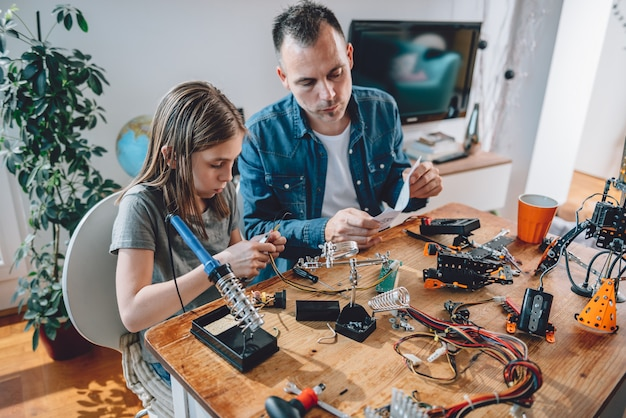 Pai e filha trabalhando em componentes eletrônicos