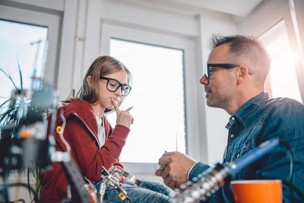 Pai e filha trabalhando juntos na oficina