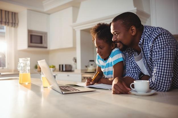 Pai e filha usando laptop enquanto tomando café