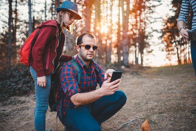 Pai e filha usando telefone inteligente na floresta