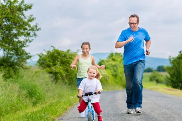 Pai e filhas correndo na rua