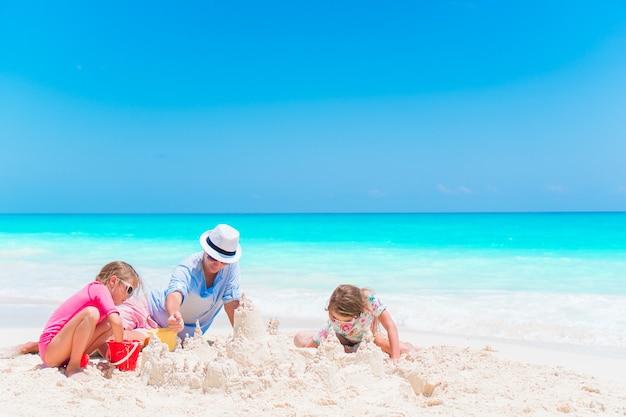 Pai e filhas fazendo castelo de areia na praia tropical