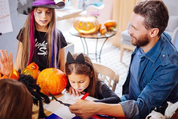 Pai e filhas. pai bonito e sorridente ajudando suas filhas a colorir fotos para o halloween