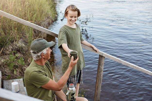 Pai e filho a passar tempo juntos na margem do rio ou lago, homem sênior dando uma xícara de chá de garrafa térmica para seu neto, família posando nas escadas de madeira que levam à água, descansar na bela natureza.