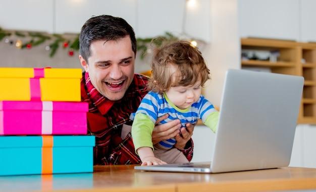Pai e filho à procura de presentes de natal no computador portátil, sentado na cozinha em casa.