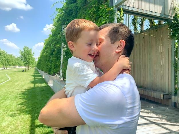 Pai e filho abraçados conversando andando no parque foto de alta qualidade