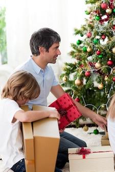 Pai e filho abrindo os presentes de natal