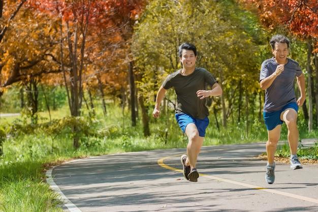Pai e filho adulto correndo juntos no caminho do parque