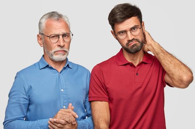Pai e filho adulto posando contra a parede branca