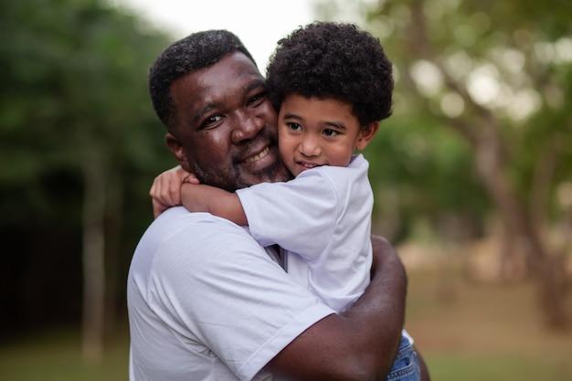 Pai e filho afro, abraçados no parque. dia dos pais.