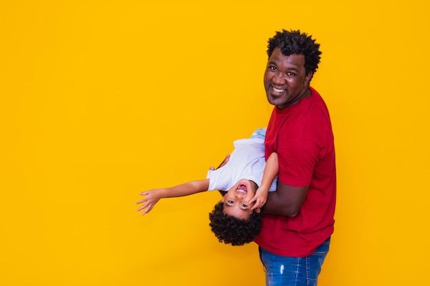 Pai e filho afro em fundo amarelo, sorrindo e brincando. conceito do dia dos pais