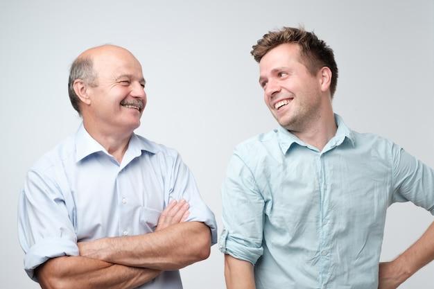 Pai e filho alegres olhando um para o outro sorrindo