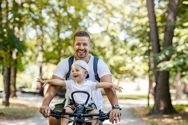 Pai e filho andam de bicicleta. as crianças pequenas sentam-se em uma cesta de bicicletas e vagam. dia ensolarado de verão com a família, hora de criar laços familiares. fim de semana em família ativo, férias no parque com a família