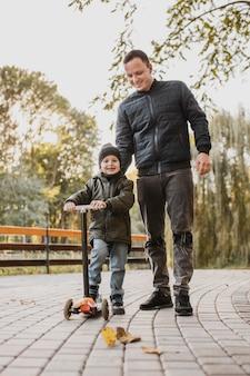 Pai e filho andando de scooter infantil