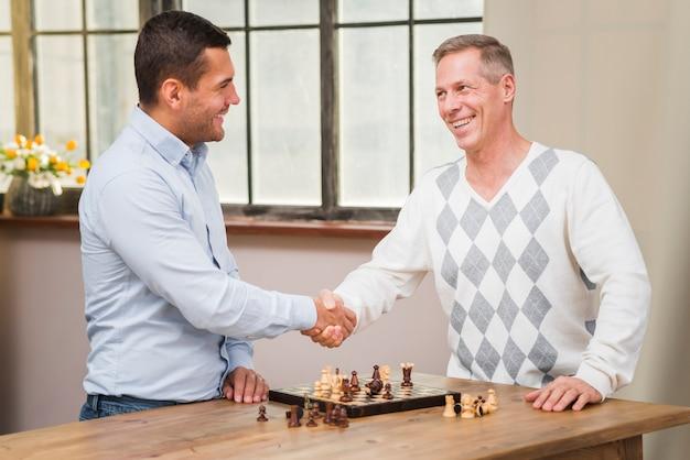 Pai e filho, apertando a mão depois de uma partida de xadrez