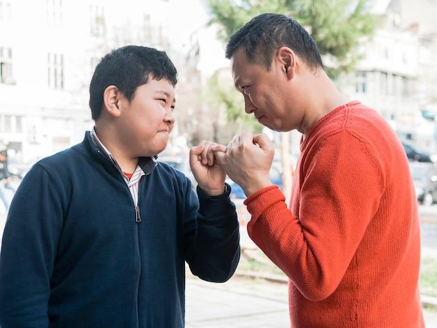Pai e filho asiáticos fazendo uma promessa