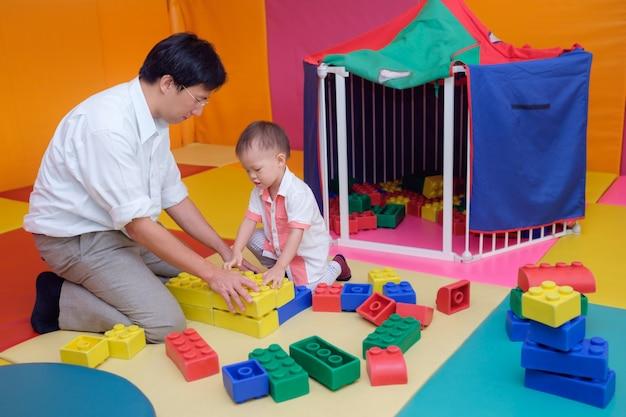 Pai e filho asiáticos se divertindo brincando com grandes blocos de plástico coloridos internos