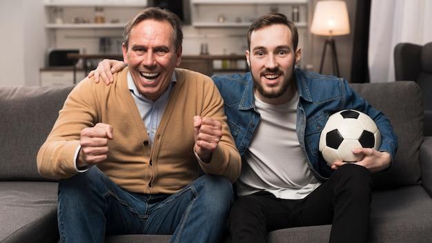 Pai e filho assistindo esportes