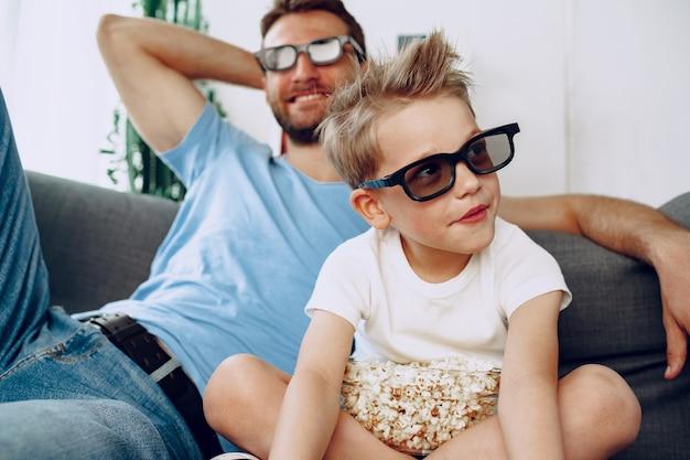 Pai e filho assistindo filmes em casa com óculos 3d e comendo pipoca