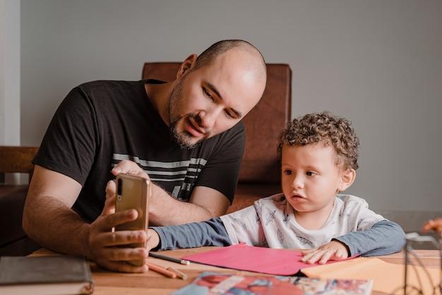 Pai e filho assistindo no celular desenhos para fazer nas folhas coloridas