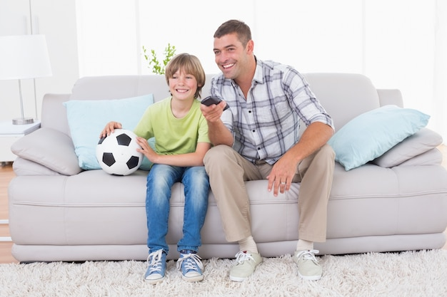Pai e filho assistindo partida de futebol no sofá