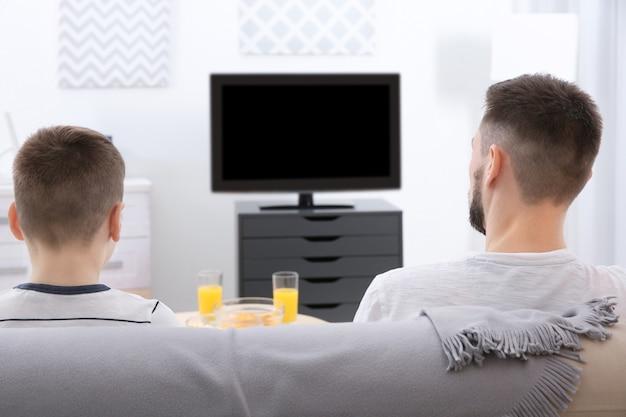 Pai e filho assistindo tv em casa