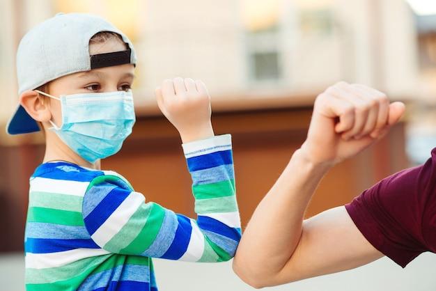 Pai e filho batem nos cotovelos ao ar livre. quarentena do coronavírus. conceito de distanciamento social.