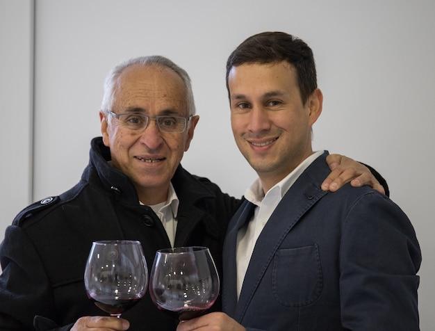 Pai e filho bebendo uma taça de vinho na cozinha de casa Foto Premium