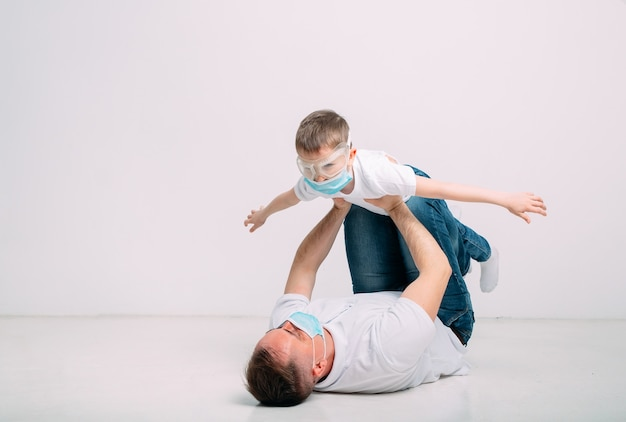 Pai e filho brincam durante a quarentena em máscaras médicas.