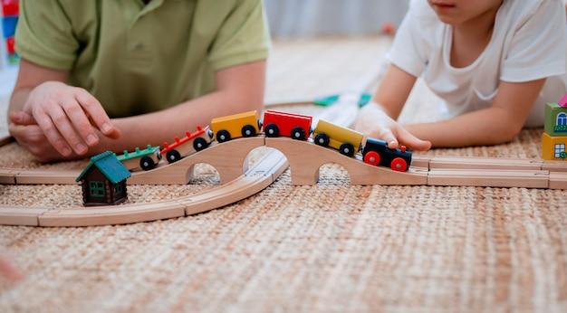 Pai e filho brincam em uma estrada de ferro de brinquedo de madeira na sala de jogos.