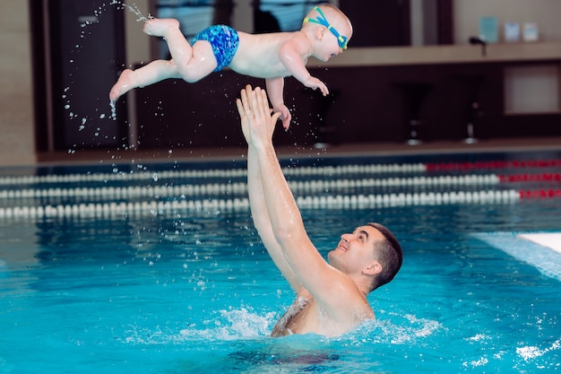 Pai e filho brincam na piscina. o pai joga o filho.