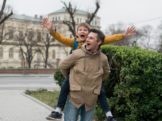 Pai e filho brincando ao lado de um parque